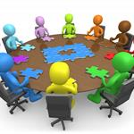Graphic of rainbow-colored featureless people sitting at a table and collaborating on a puzzle