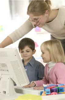 A boy and a girl sitting in front of an older computer with a woman standing behind them